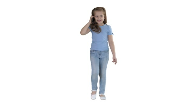 Little cute girl making a phone call while walking on white background