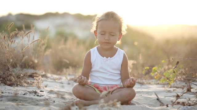 Little cute girl meditates outdoor at sunset with beautiful natural light Little cute girl meditates on the sand dunes at sunset with beautiful natural light. zen like stock videos & royalty-free footage