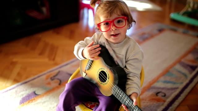 vídeos de stock e filmes b-roll de pouco fofinho menina a tocar e cantar guitarra de brinquedo - instrumento musical