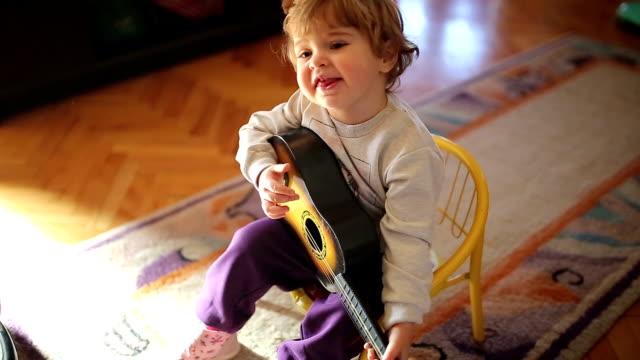 stockvideo's en b-roll-footage met weinig schattig meisje spelen speelgoed gitaar en zang - speelgoed