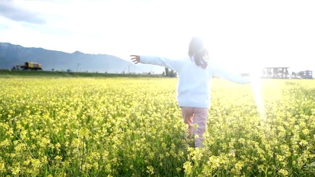 liten söt flicka kör i blommor - tillgiven bildbanksvideor och videomaterial från bakom kulisserna