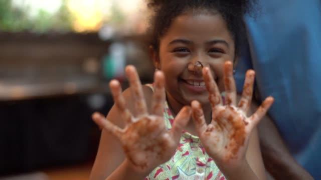 vídeos y material grabado en eventos de stock de niña linda mostrando sus manos chocolate - desordenado