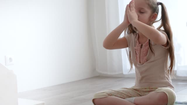 little cute girl sitting in yoga lotus pose and meditates near the window little cute girl sitting in yoga pose and meditates on the window sill at light room with natural light. Child sitting in lotus pose with closed yeys. mental wellbeing stock videos & royalty-free footage