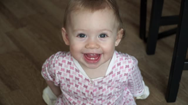 Little cute girl takes off her head clothes smiling and laughing. Smile first lower teeth Little cute girl takes off her head clothes smiling and laughing. Smile first lower teeth first occurrence stock videos & royalty-free footage