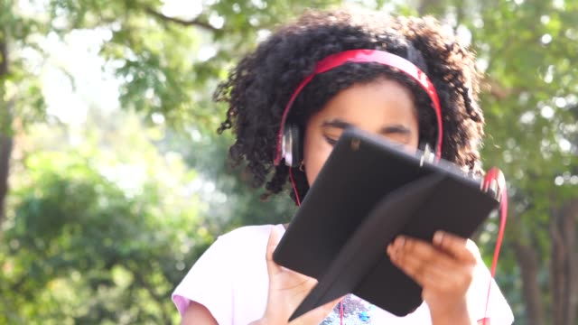 vídeos de stock, filmes e b-roll de menina bonita usando tablet no parque - brasileiro pardo
