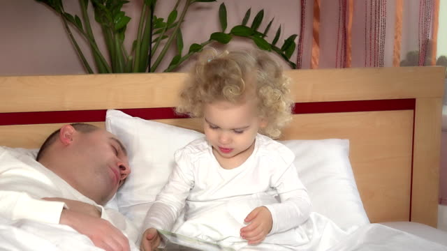 Little cute girl wake up her father sleeping and embrace hug in bed video