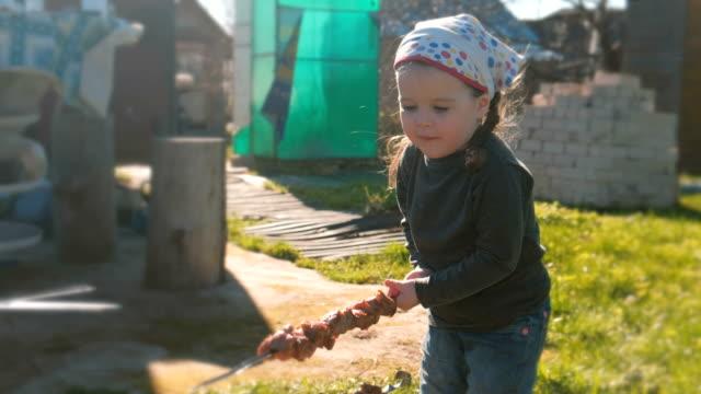 かわいい女の子は、串バーベキュー シャシリクを食べたいと。 - ブタ点の映像素材/bロール