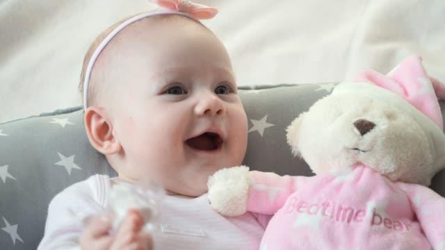 vídeos de stock e filmes b-roll de little cute girl with pink toy teddy bear laughs and smiles - teddy bear