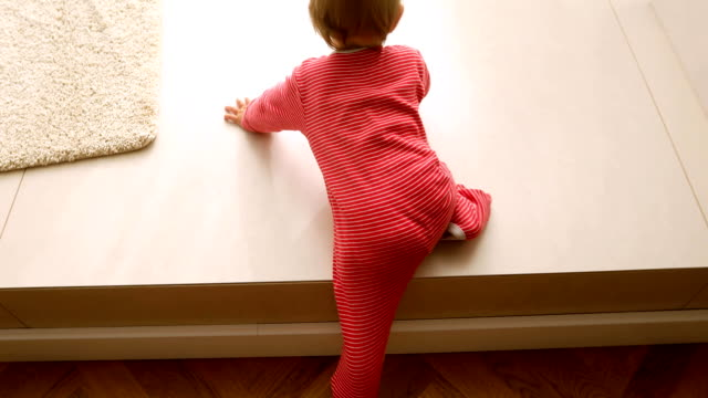 自宅で階段に登る小さなかわいい幼児の女の子 - 階段点の映像素材/bロール