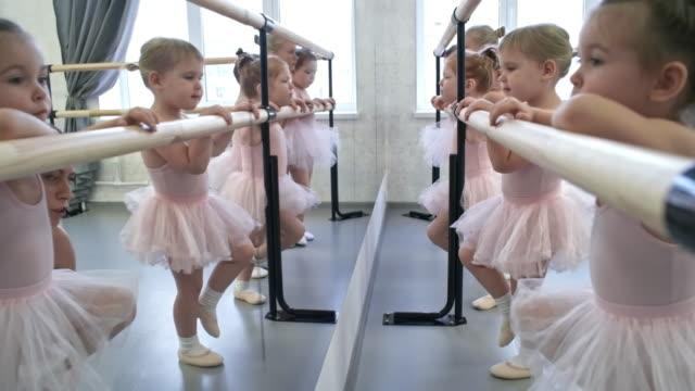 vídeos de stock e filmes b-roll de little dancers standing at ballet barre - tule têxtil