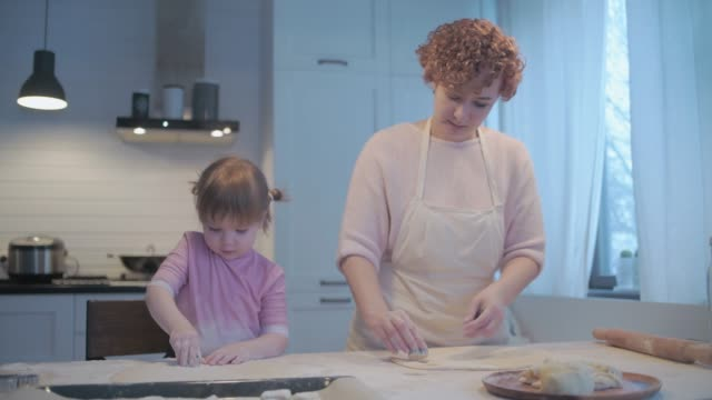 vídeos de stock e filmes b-roll de little daughter helps mom in the kitchen with baking. cut the cookies with cookie cutters. spread cookie blanks on baking paper. - baking bread at home