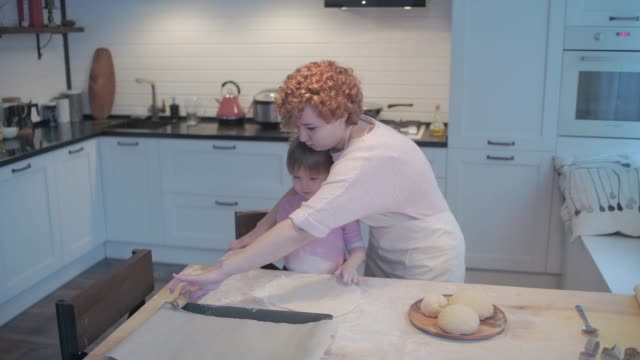 little daughter helps mom in the kitchen with baking. knead the dough together. - formare pane video stock e b–roll