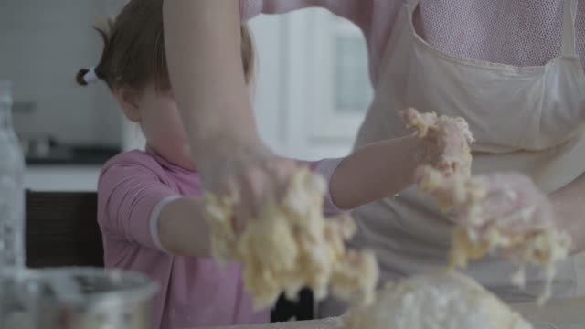 vídeos de stock e filmes b-roll de little daughter helps mom in the kitchen with baking. knead the dough together. - baking bread at home