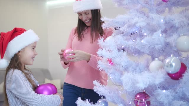 Little daughter holds a lot of pink glass baubles, her mother takes baubles and decorates a fir-tree.
