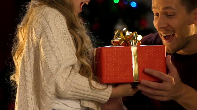 lilla dotter presentera x-mas present till far, söt flicka kramar kärleksfull pappa - christmas gift family bildbanksvideor och videomaterial från bakom kulisserna