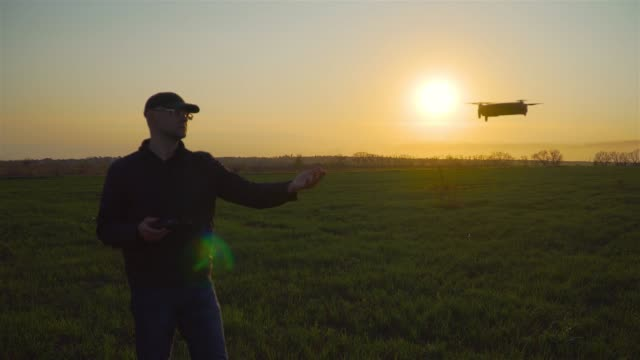 Little drone flying near young caucasian glassed man with outstretched hand at sunset