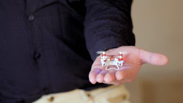 liten drönare svävar ovanför handen, flyger från hand - liten bildbanksvideor och videomaterial från bakom kulisserna