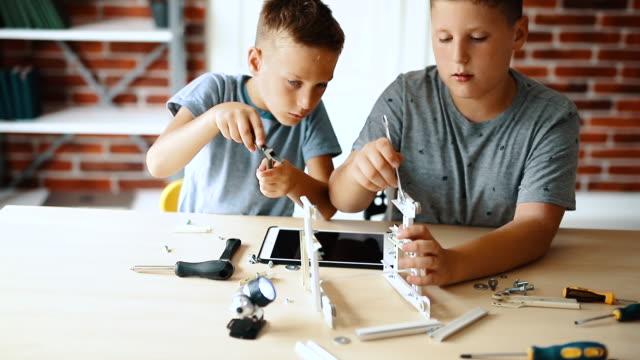 маленькие инженеры! дети младшего возраста сотрудничают в создании «робота». - манипулятор робота производственное оборудование стоковые видео и кадры b-roll