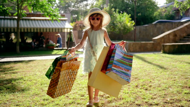 little fashion-girl with shopping bags after visiting expensive boutiques walks on lawn and smiles little fashion-girl with shopping bags after visiting expensive boutiques walks on lawn and smiles in sunlight large group of objects stock videos & royalty-free footage