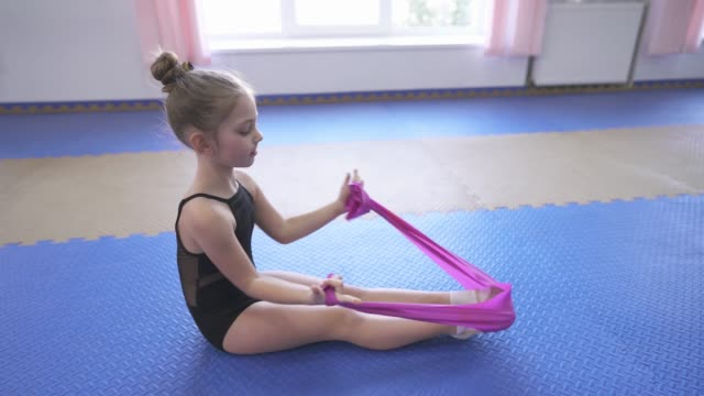 Little female gymnast doing stretching exercises in the gym while training (exercises with gymnastics stretch strap).