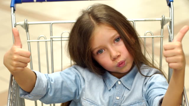 Little funny girl sits in a grocery cart in a supermarket and shows her thumb up