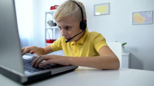 stockvideo's en b-roll-footage met kleine gamer in headset spelen op laptop moeder zetten boeken op bureau en scolding - kids online abuse