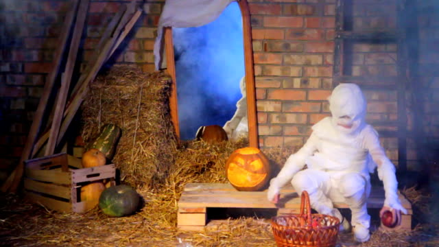 Little Ghost Picking Up Apples Scattered By Children At Halloween Holiday video