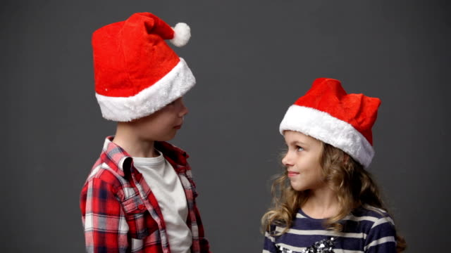 Little girl and boy in christmas caps video
