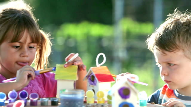 Little girl and boy painting birdhouses video