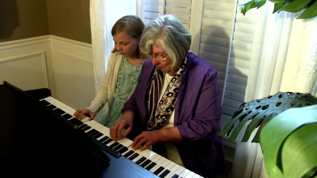 Little girl and grandma play piano then hug video