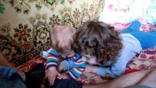 Petite fille et sa petite sœur jouant avec jambe de pères - Vidéo
