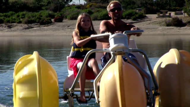 Little girl and her father riding a large water bike video