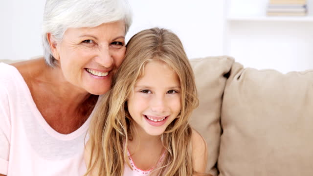 Little Girl and Her Grandmother HD: Grandmother and granddaughter smile as they hold their heads together. granddaughter stock videos & royalty-free footage