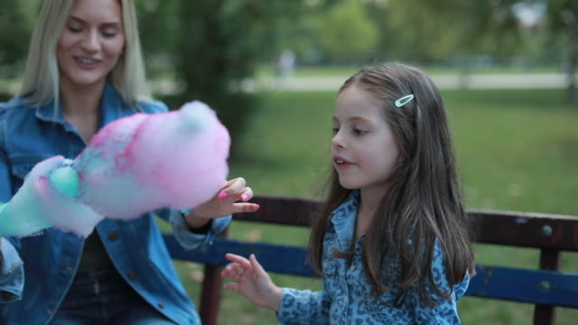 Little girl and her mom eating cotton candy Mom feeding cute girl with sticky cotton candy cotton candy stock videos & royalty-free footage