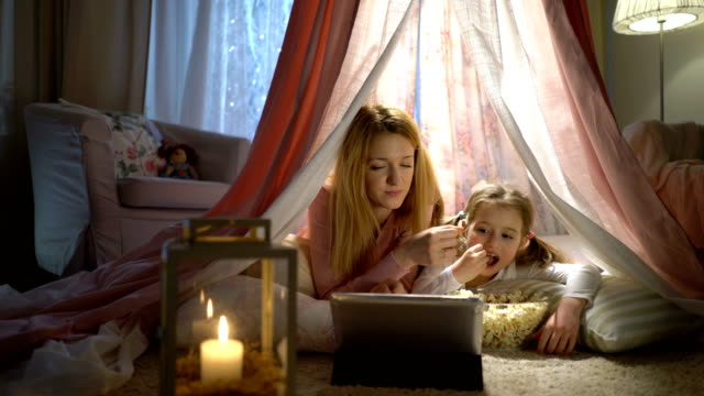 Little girl and her mom enjoying watching cartoons online in the tent in the nursery Family movie theater. Little girl and her mother enjoying watching cartoons online and eating popcorn in the tent in the nursery family watching tv stock videos & royalty-free footage