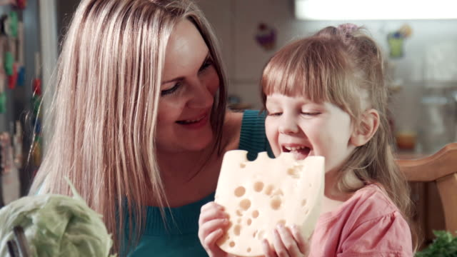 Little girl and her mother biting cheese with holes Beautiful mother and cute daughter at home in kitchen, biting tasting cheese and looking at camera and smiling. They are very happy and cheerful. cheese stock videos & royalty-free footage