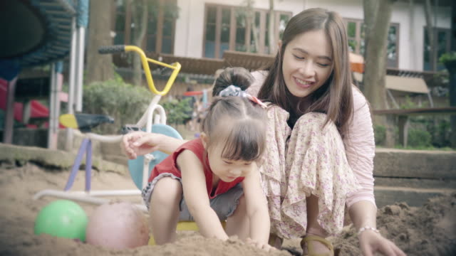 Little girl and her mother playing in the playground. video
