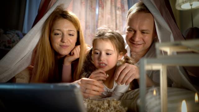 stockvideo's en b-roll-footage met klein meisje en haar ouders genieten van het kijken naar cartoons online in de tent in de kwekerij - popcorn