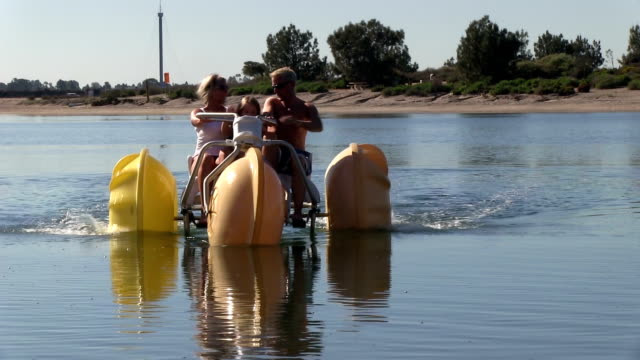 Little girl and her parents riding a large water bike video