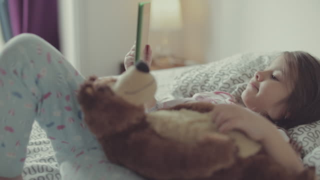 Little girl and her teddy bear watching tablet
