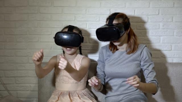 vídeos de stock, filmes e b-roll de uma garotinha e sua irmã adolescente em óculos de realidade virtual sentado e jogando jogos virtuais em casa no sofá sobre um fundo branco. eles balance suas mãos e olhem ao redor. close-up. 4 k. 25 fps. - mobile