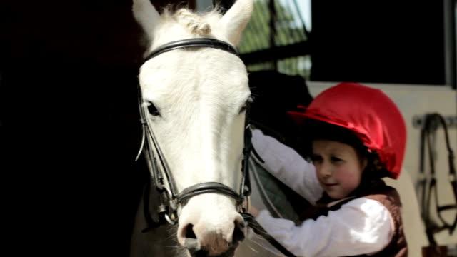 ritratto: piccola ragazza e cavallo - attività equestre ricreativa video stock e b–roll