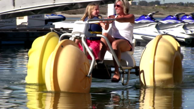 Little girl and mother riding a large water bike video