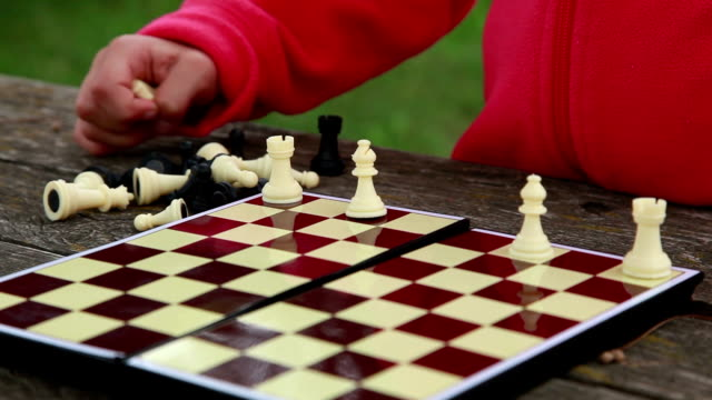 Little girl arranging white chess pieces on the chessboard