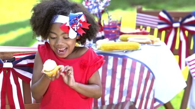 Little girl at July Fourth picnic enjoying cupcake A cute little mixed race 7 year old girl at a Fourth of July or Memorial day picnic eating a cupcake. She is savoring every bite. fourth of july videos stock videos & royalty-free footage