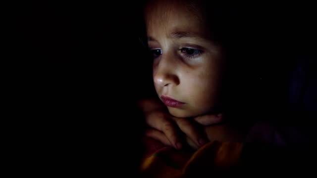 vídeos de stock e filmes b-roll de little girl at night watching cartoons - tv e familia e ecrã