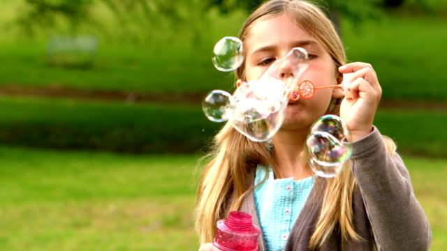 Little girl blowing bubbles in the park Little girl blowing bubbles in the park in slow motion pigtails stock videos & royalty-free footage