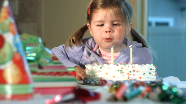 Little girl blowing out birthday candles, slow motion video