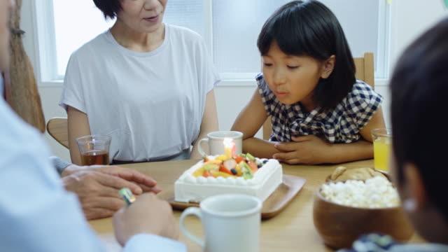 家族の誕生日ディナーで蝋燭を吹く少女 ビデオ