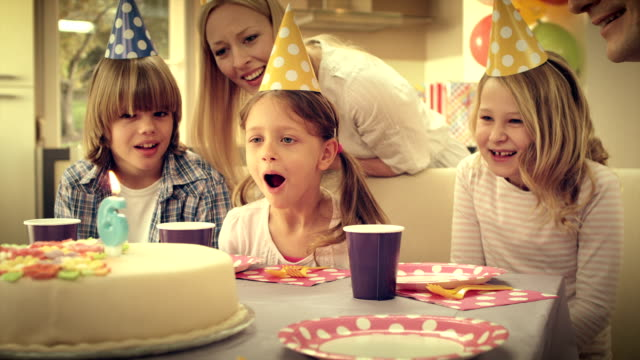 SLO MO little girl blowing out candles on birthday cake video